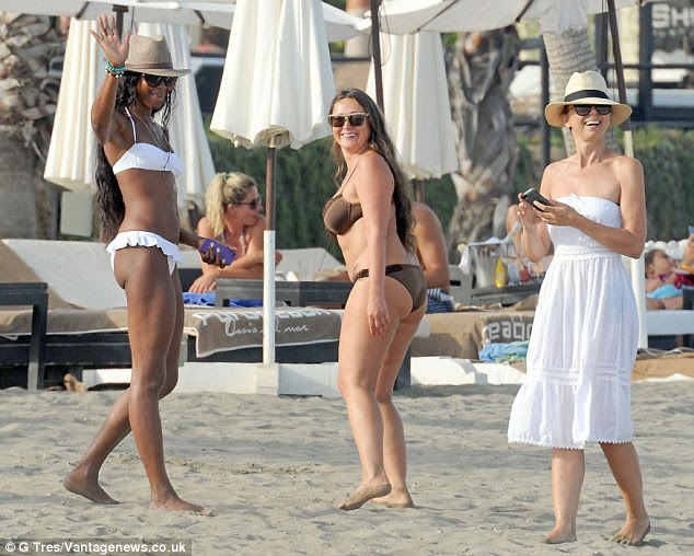 Fun in the sun: The 43-year-old supermodel looked the picture of contentment as she joined two pals for a stroll along the sand, laughing and joking as she made her way to a sun lounger