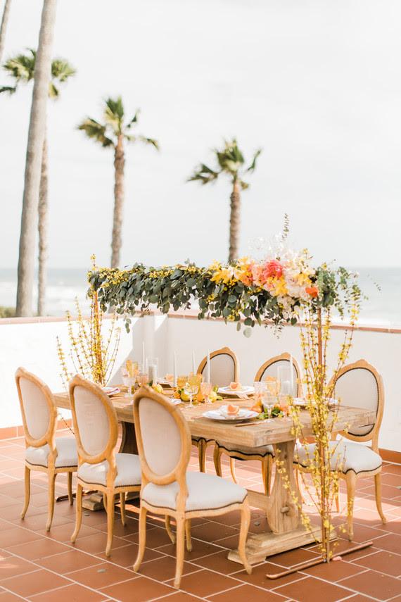 Hochzeit Tisch war dekoriert mit laub, Fett gelb, rosa und blush-Blüte Tisch-Läufer befestigt, über den Tisch