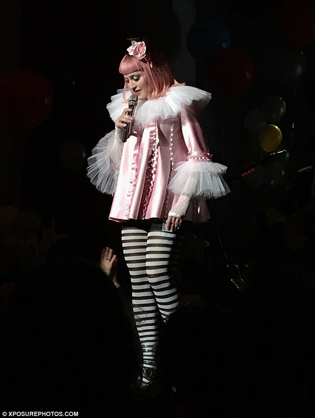 Pretty in pink! Clad in striped stockings and pink heels, she made a show of strutting around the room in her pink smock and ruff