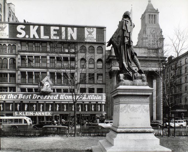 Union Square, Manhattan. Looking up at statue of Lafayette from behind and left, S. Klein's store, a bank, a hotel and the Consolidated Edison Building, beyond.