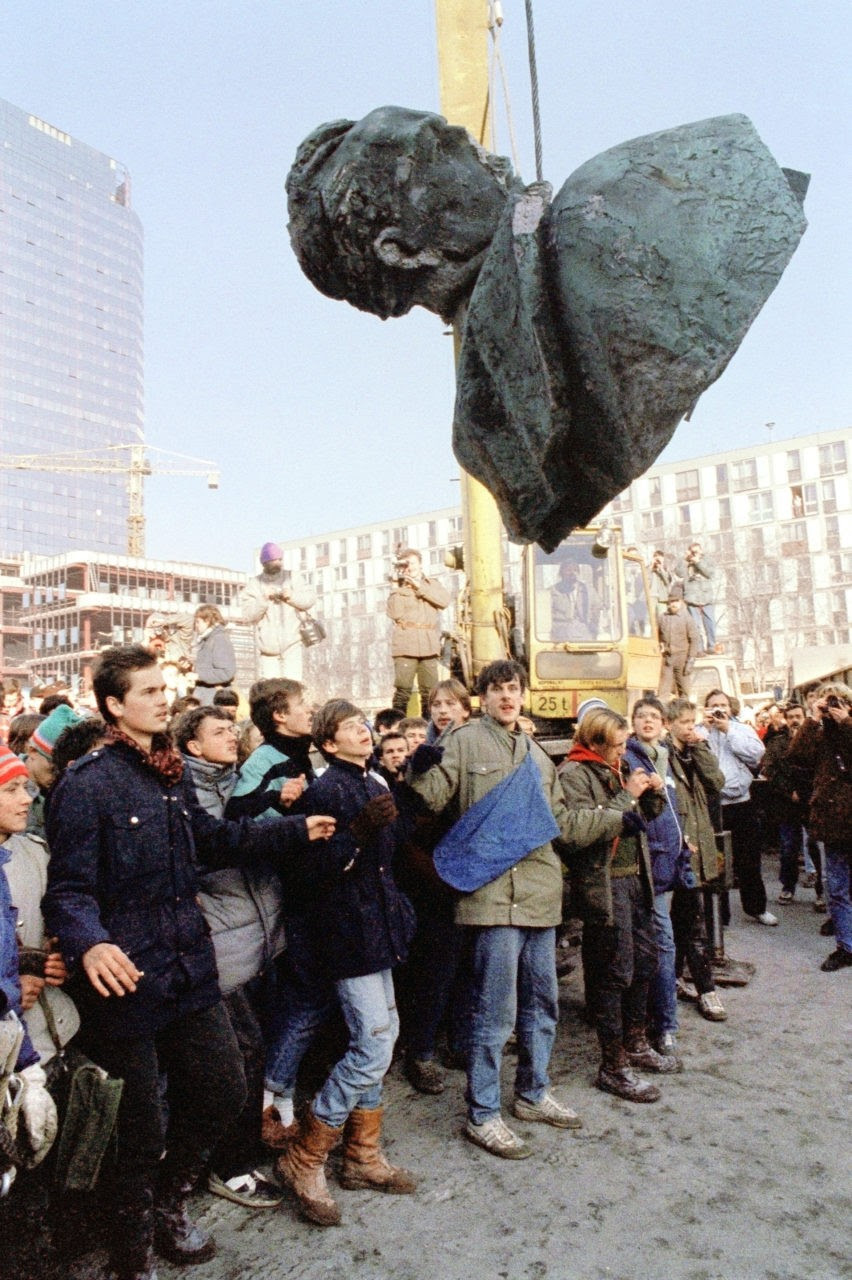 People applaud 17 November 1989 in Warsaw as the 15m (49ft) statue of Felix Dzerzhinsky, the founder of Cheka, the first Soviet's secret service, is taken down. The statue had stood in a square named after Dzerzhinsky in downtown Warsaw since 1945. This was the latest of several statues of former communist leaders to be removed here since a non-communist government came to power in September 1989. (Photo credit should read WOJTEK DRUSZCZ/AFP/Getty Images)
