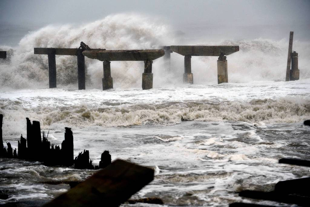 Waves crash against a previously damaged pier before landfall of Hurricane Sandy in Atlantic City, New Jersey. Storm-driven waves crashed ashore and flooded seafront communities across a swathe of the eastern United States as Hurricane Sandy barreled towards land. Officials warned that the threat to life and property was