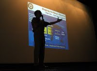 US Navy 040605-N-6633C-002 Commander Naval Reserve Force, Vice Adm. John G. Cotton, is silhouetted in front of a Powerpoint slide mapping out the Naval Reserve Force's future