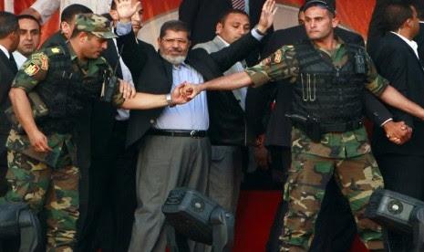 Mohamed Mursi (tengah) melambaikan tangan ke para pendukungnya saat ditahan oleh anggota keamanan presiden di Tahrir Square, Kairo, Mesir, pada 29 Juni 2012. (file foto).