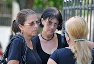 Ofelia Acevedo (L) widow of the late Cuban dissident Oswaldo Paya, talks with relatives after a mass at Salvador del Mundo Church in Havana. Acevedo has rejected a government report that blamed the car crash that killed her husband on the driver, saying she had been denied access to information. (AFP Photo/Adalberto Roque)