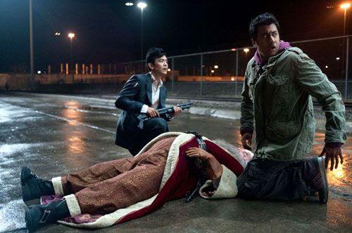 Harold (John Cho) and Kumar (Kal Penn) tend to Santa Claus after Harold accidentally shoots him in the head with a shotgun in A VERY HAROLD & KUMAR 3D CHRISTMAS.