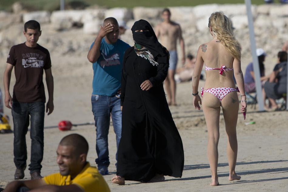 Παλαιστίνιοι και οι Ισραηλινοί απολαμβάνουν την ηλιόλουστη  μέρα σε παραλία στη Μεσόγειο Θάλασσα κατά τη διάρκεια της πρώτης ημέρας του φεστιβάλ Eid al-Fitr στο Τελ Αβίβ. (AP Photo / Oded Balilty)