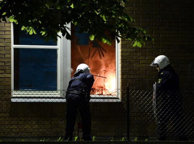 Bombeiros apagam fogo em escola de subúrbio de Estocolmo, capital da Suécia, na madrugada deste sábado (25) (Foto: AFP)