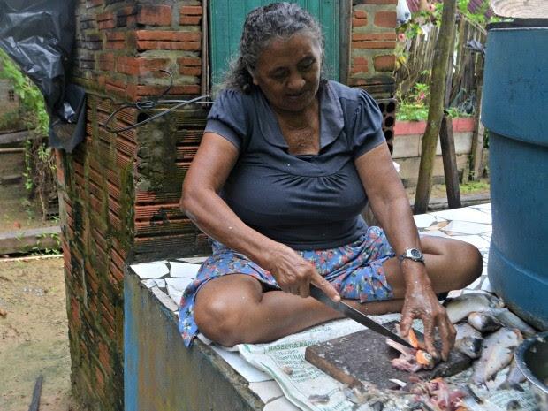 Ângela cuida do peixe que deve ser consumido durante a Semana Santa  (Foto: Taís Nascimento/G1)