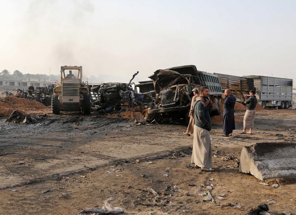 Civis inspecionam caminhão que explodiu durante ataque suicida no Sul de Bagdá, no Iraque, nesta quinta-feira (30)  (Foto: Karim Kadim/ AP)