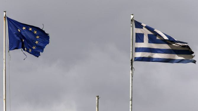 Frayed EU and Greek flags flutter atop the Greek Ministry of Finance in central Athens