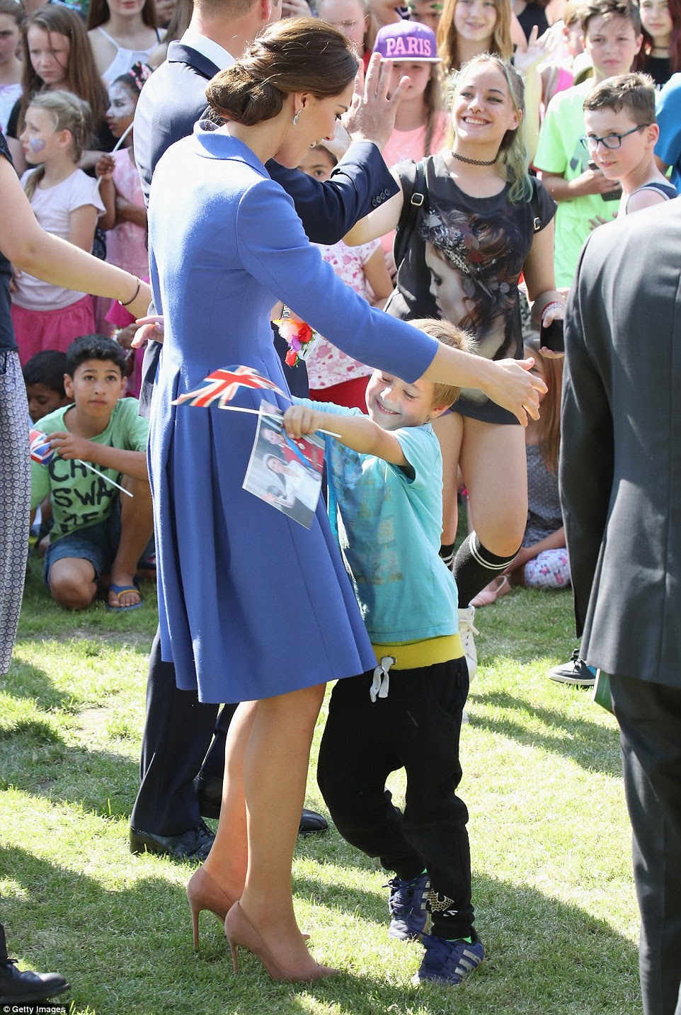 The Duchess received a rapturous welcome from a young royal fan on a visit to a children's charity in Berlin this afternoon, who was clutching a picture of her wedding to Prince William