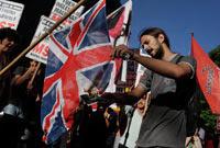 Un hombre quema una  bandera británica frente al edificio del Ministerio de Asuntos  Exteriores en Buenos Aires reclamando la soberanía de las islas  Malvinas. Foto: AP