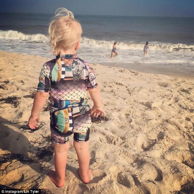 amor do bebê: Uma imagem mostrou a gracinha loira vestida com um terno molhado colorido enquanto olhava as ondas do mar e um par de meninas mais velhas brincando na água rasa