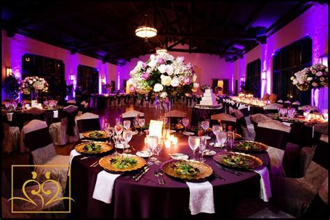 Purple tablecloths with white tall centerpieces   Dana's