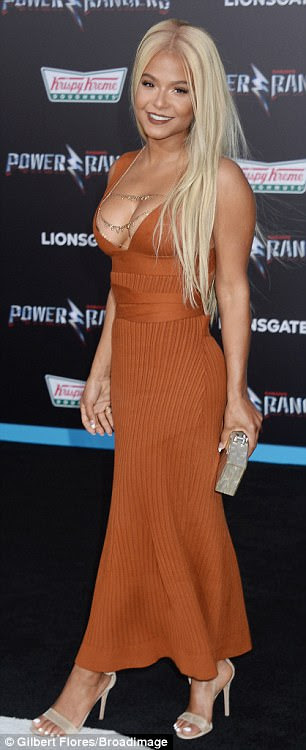 Standing out! The 35-year-old songstress put on a busty display in a rust orange gown with cut-outs on the back