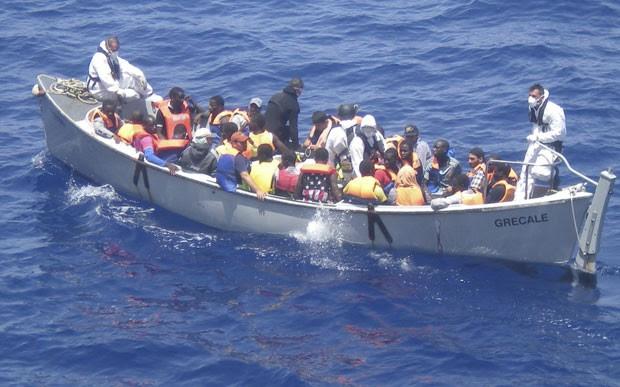Imigrantes são resgatados de barco que levava cerca de 600 pessoas na costa da Itália. Cerca de 30 morreram asfixiados (Foto: Marinha da Itália/AP)