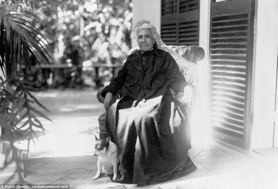 A striking portrait of Liliuokalani, Queen of Hawaii, seated outdoors with her dog in a picture taken around 1917