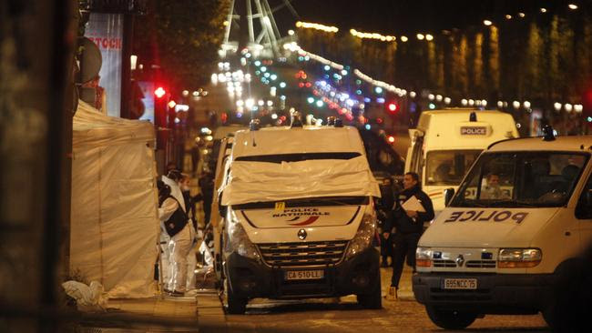 Forensic experts and police officers examine evidence from a police van on the Champs Elysees in Paris. Picture: AP
