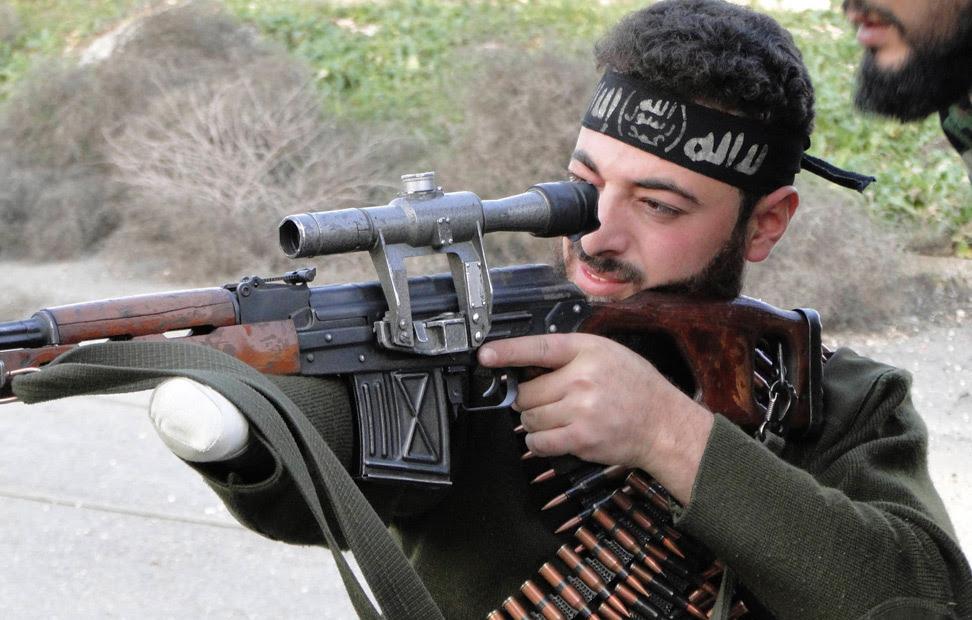 Un combatiente del Ejército Libre de Siria, con una mano amputada, apunta su arma hacía las fuerzas leales al presidente de Siria, Bashar al-Assad, en el aeropuerto militar de Menagh, en los alrededores de Alepo.