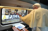 """In this picture made available by the Vatican newspaper Osservatore Romano, Pope Benedict XVI salutes from the train's window as he arrives for a peace meeting in Assisi, central Italy, Thursday, Oct. 27, 2011. The pontiff has invited Jews, Hindus, Sikhs and Muslims to a pilgrimmage to the Umbrian hilltop town of Assisi where 25 years ago Pope John Paul II, the Dalai Lama and others spent the day praying for peace amid the Cold War. The banner in background reads """"Peace"""". (AP Photo/Osservatore Romano) EDITORIAL USE ONLY"""