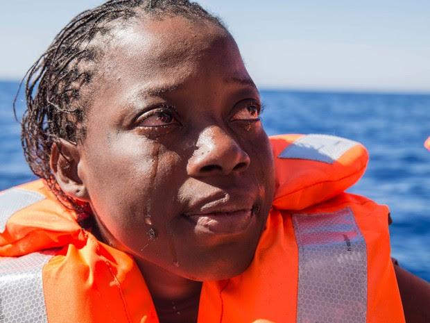 Mulher resgatada durante travessia da Líbia até a Europa chora  (Foto: Anna Surinyach/MSF)