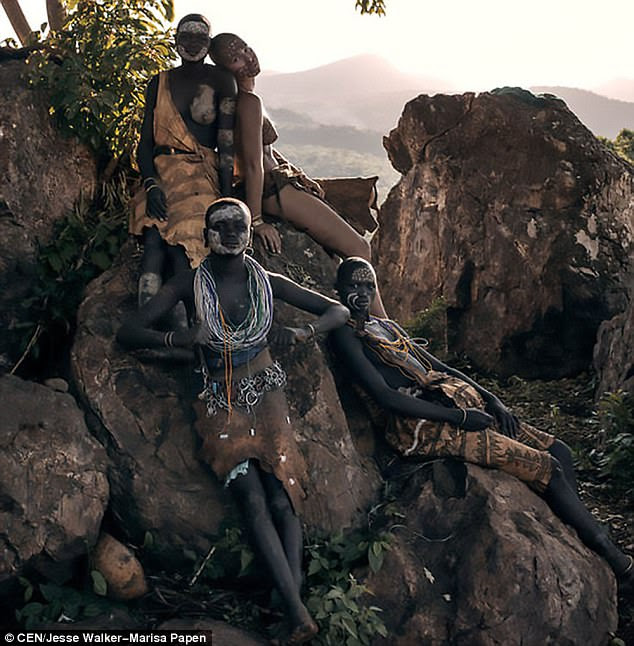 A naked Papen poses on a rock with three members of the tribe who are all adorned in their traditional attire