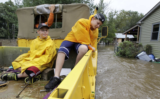 William Pillus, 13, right, and his brother Michael Pillus, 10, ride in the back of their neighbor Gary Leusink's truck as they ride into Leusink's property through floodwaters from Hurricane Irene, Su