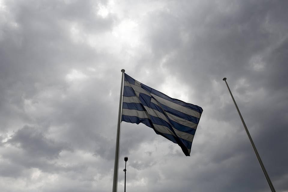 A Greek national flag flies outside the Athens Stock Exchange SA on Aug. 21.