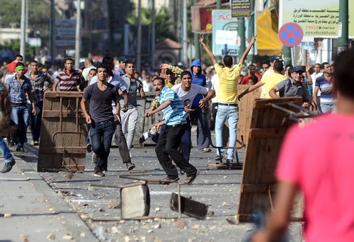 Supporters of the Muslim Brotherhood and Egypt's ousted president Mohamed Morsi clash with opponents to ousted president Morsi (not in picture) in the Mediterranean city of Alexandria on July 26, 2013. by Pan-African News Wire File Photos