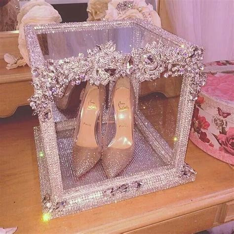 A blinged out glass display box for a pair of louboutin