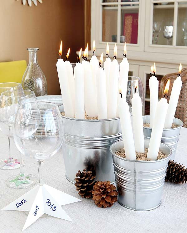 White candles in sand filled buckets