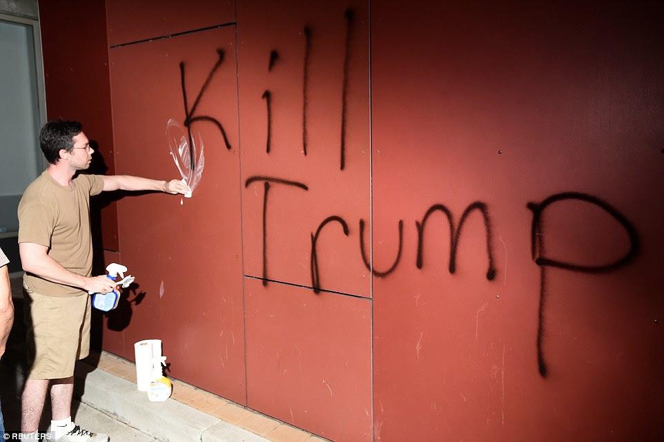 Oakland:A member of the public tries toscrub away 'Kill Trump' graffiti as demonstrators riot in California