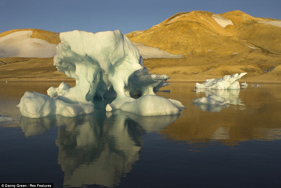 This iceberg, in Svalbard, Norway, sits peacefully on the  glass-like waters of an arctic lake