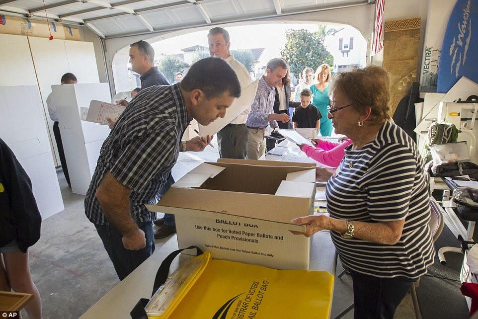 estação de garagem: Trabalhador Poll Bea Iwig ajuda a primeira vez eleitor John Wickenhiser completar sua cédula em San Diego
