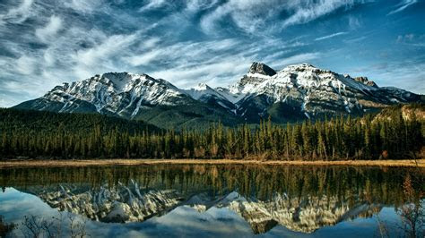 peaceful mountain lake pine forest  green trees snowy mountains  blue sky  white