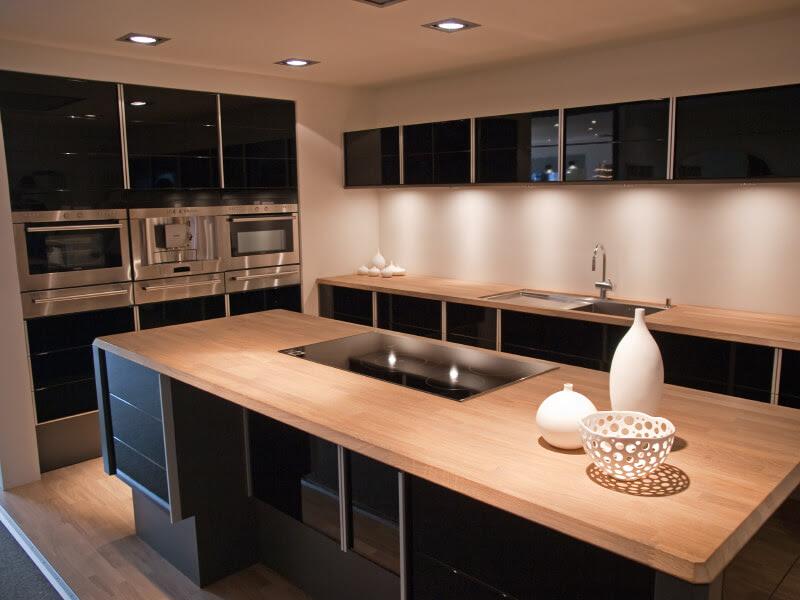 Cuisine contemporaine avec armoires noires et en acier inoxydable et comptoirs en bois clair