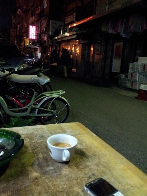 Taipei: Coffee shop in the back alley 台北:暗闇のなかの珈琲屋 昔、といっても日本がバブル景気で大騒ぎしていたころ、東アジア世紀末研究会と名うって仲間を集めては旅をしまくっていた。アジアで一人勝ちだった日本、他の周辺国は戦争の勝者であったにもかかわらず、敗戦国の発展ぶりを苦々しく眺めていたころだ。それらの国は街が薄暗かった。旅に参加したその中の一人、彫刻家の方がこう漏らした。「日本の都会は暗闇がなくなってしまったよなー」と。 八十年以降、台湾は高度成長期に入る。民主化が進み、あれほど「反攻大陸」と叫んでいたことが嘘のように消え去っていった。それとともに街は明るくなっていく。少ない街灯の下で、歩くと影が動いていく、そんな風景も見られなくなっていった、と思っていたが、未だ街中の、それも目抜き通りの裏に残されていた。 最近、週末ともなると地下鉄雙連駅脇の公園通りの青空市場で一軒一軒屋台の物売り屋を覗いている。ある昼下がり、ふと脇の路地裏に入り込んだところ、らしくない看板が目に付いた。「エスプレッソ」。場違いじゃろが…。間口三メートル足らず、店先に小さなテーブルが一つ、椅子が三脚。店の中は雑然とあれやこれやが並んでいて通り抜けるのがようやっと。奥は深くてうなぎの寝床状態。 珈琲豆と機械のの卸を兼ねてコーヒーを飲ませているらしい。「いらっしゃい、何を飲みますか?」とメニューを持ってくるも、私はネオン看板の「エスプレッソ」を指差し「量は?」と問う。店主「ダブルだけです」。注文する。エスプレッソ・マシンからの音が店内から聞こえてまもなく、小さなテーブルにソーサーも付かずにカップは運ばれてきた。味は?悪くない、いや旨い。 支払いの段になって、百元前後だろうと、日本円三百円ほど、と思いきや、「五十元です」。コンビニの大カップ五十元と同じである。私は時あらば訪れることにした。そしてベトナム・ネールサロンのネオンサインと暗闇の残る路地裏でエスプレッソを味わってきた。ベジタリアン・レストラン、菜食飯屋のあとのディナー・コーヒーを。
