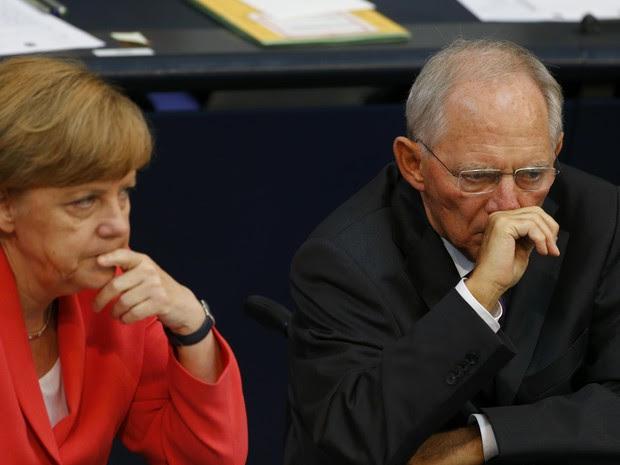 A chanceler alemã, Angela Merkel, e o ministreo das Finanças do país, Wolfgang Schaeuble, durante sessão no Parlamento em Berlim, na sexta-feira (17) (Foto: REUTERS/Axel Schmidt)