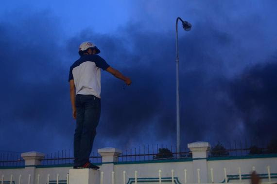 A man stands on a wall to watch smoke from a damaged Chinese owned shoe factory in Vietnam's southern Binh Duong province May 14, 2014. REUTERS-Thanh Tung Truong