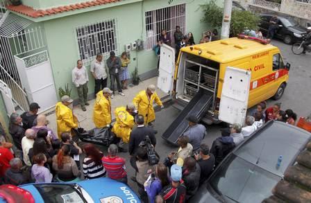 Os corpos sendo retirados da casa onde ocorreu o crime