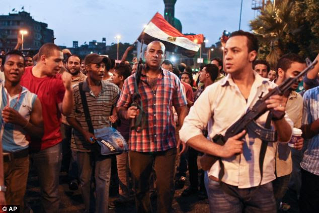 Plain-clothes policemen walk with protestors opposed to Egyptian President Mohammed Morsi at the site of clashes with opposing protestors in the Kit Kat neighborhood of Giza, Egypt