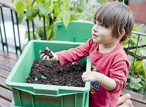 O garoto Micah Spínola, 1, brinca com terra em minhocário
