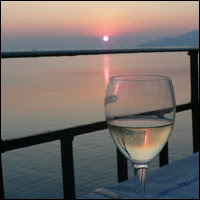 A solitary glass of chilled white wine on a table outdoors with a beautiful sunset as a backdrop.