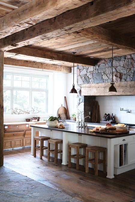 Nature Inspired Kitchen Wall An earth friendly kitchen in stone, wood and tile. The stone wall in this rustic kitchen is highlighted by salvaged wood beams and white tile. Floor made from flagstone and reclaimed hemlock wood mirrors the stone wall panel and timber ceiling. A painted white island with a stone top is used for food prep, add teak stools so it can double as a seating area. Pendant lighting that is simple makes it modern. Photography: Angus FergussonRoom design: Jill Kantelberg
