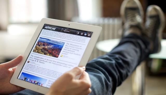 Hombre-con-los-pies-puestos-en-una-mesa-leyendo-unas-noticias-en-su-tablet