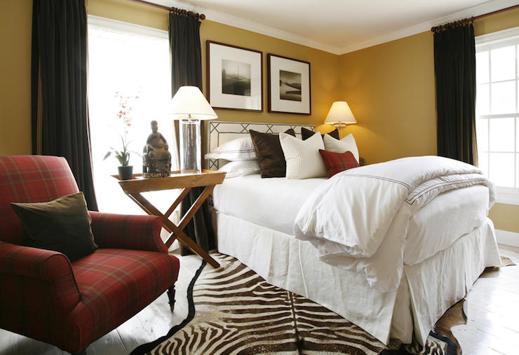 bedrooms - chocolate brown velvet drapes pillows zebra cowhide rug red plaid chair x-base nightstand table glass column lamps white black leather headboard nailhead trim yellow walls buddha