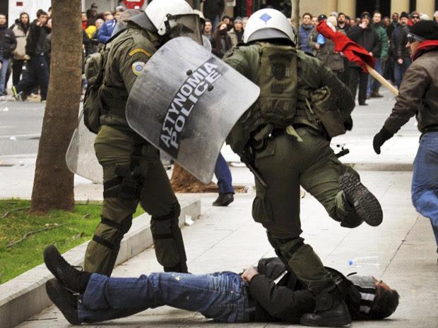 Policial chuta manifestante durante protestos em Atenas, na Grécia, nesta sexta-feira (10). (Foto: John Kolesidis/Reuters)