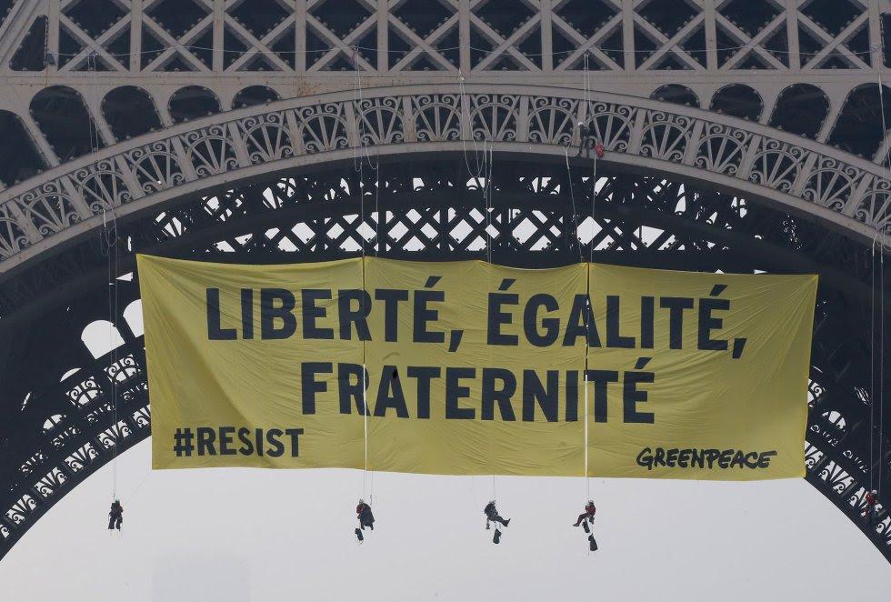 Una docena de activistas de Greenpeace han desplegado una pancarta de 300 m² desde la Torre Eiffel.