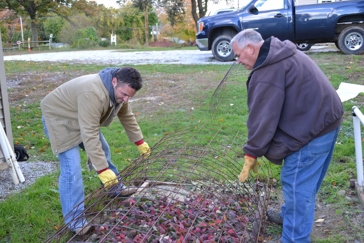 Mike and Duston McGroarty covering plants for the winter.